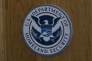 The Department of Homeland Security logo hangs in San Diego during a news conference on October 26, 2017.