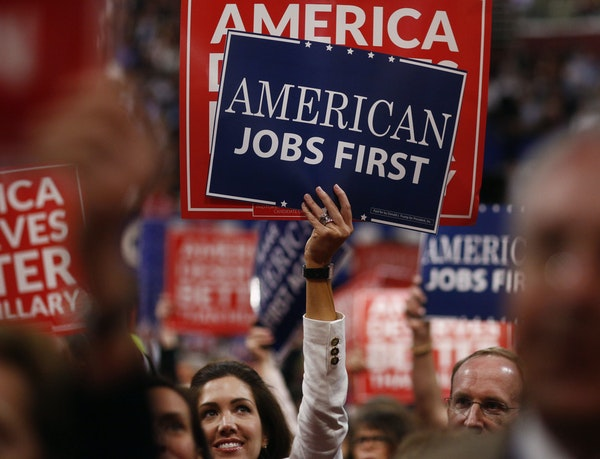 Delegates hold signs during the Republican National Convention in Cleveland on July 20, 2016. MUST CREDIT: Bloomberg photo by Andrew Harrer.