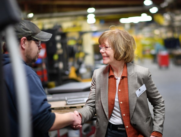 Sen. Tina Smith shook hands with a worker at Wyoming Machine in January.