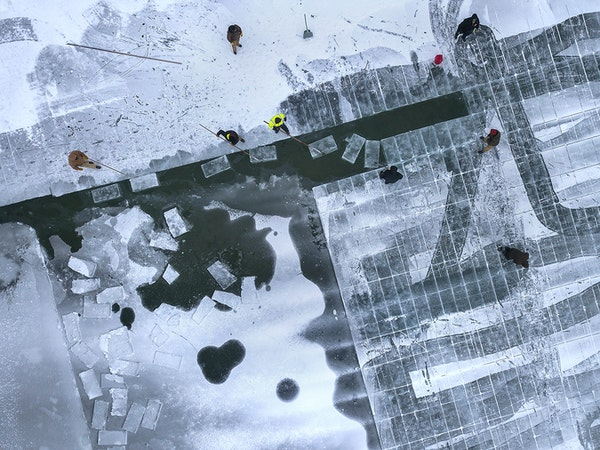 A view from above of workers harvesting 500 pound ice blocks from frozen Green Lake, near Spicer MN, The blocks are being used for the St. Paul Winter