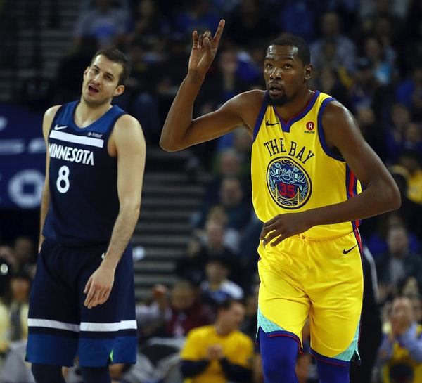 The Warriors' Kevin Durant, right, celebrated a basket as Wolves forward Nemanja Bjelica looked on with dismay in the first half.