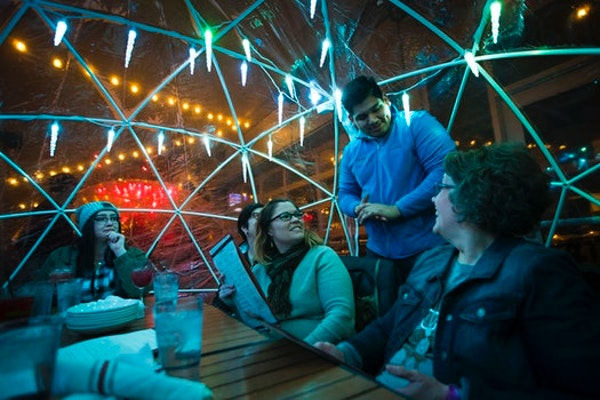 Server Peter Tazin took an order from Mayo colleagues, from the left, Hannah Wright, Jean Fox, Stacy Weelborg and Ruth Grimm in an igloo on the roofto