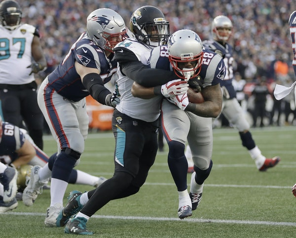 New England Patriots running back James White (28) runs against Jacksonville Jaguars linebacker Myles Jack (44) to the end zone for a touchdown during