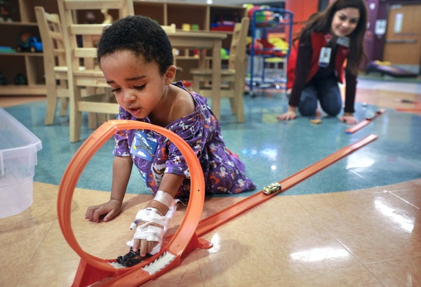 Child Life volunteer Yesica Mercado Munoz, 16, played with 2-year-old Damian Bridges, who was hospitalized for hypoglycemia at Children's Hospital i