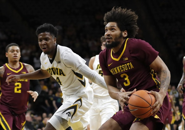 Minnesota forward Jordan Murphy (3) drives to the basket past Iowa guard Isaiah Moss, left, during the first half of an NCAA college basketball game,