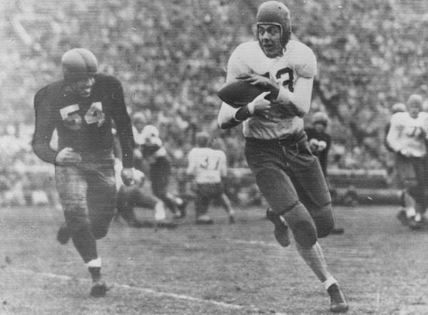 Wisconsin's Joe Kelly chases as Bud Grant grabs a pass for the Gophers in 1948. Grant would go on to play professionally for the Eagles.