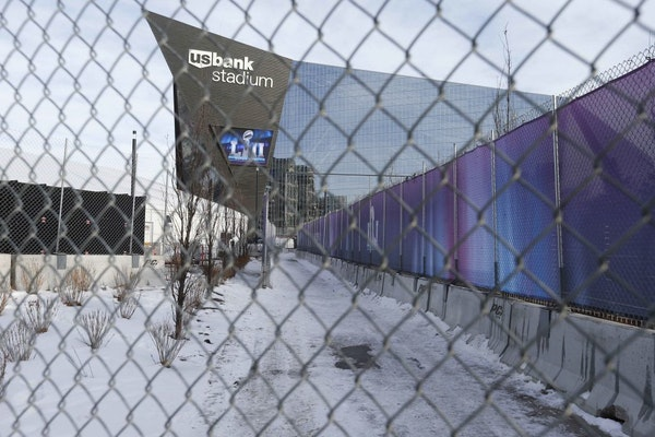 In this Jan. 18, 2018 photo, U.S. Bank Stadium, home of the upcoming Super Bowl, is seen through the protective concrete and chain link fence, part of