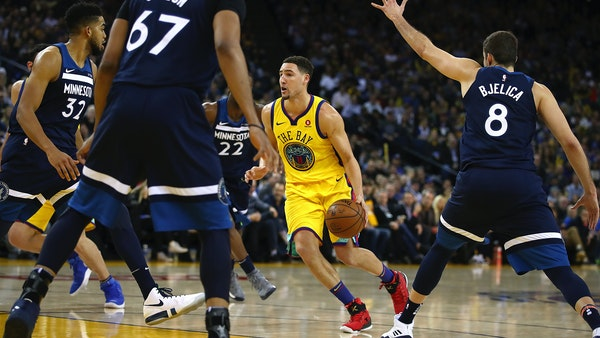 Golden State Warriors' Klay Thompson, center, drives the ball against the Minnesota Timberwolves during the second half of an NBA basketball game Thur