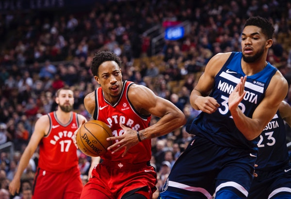 Toronto Raptors guard DeMar DeRozan (10) moves in on Minnesota Timberwolves Karl-Anthony Towns, right, during the first half of an NBA basketball game