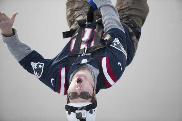 Super Bowl festivities opened Friday, including a zipline across the Mississippi River. Sporting a Patriots jersey, Paul Studer of Minnetonka dove in.