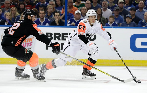 Pacific Division's Rickard Rakel, right, of the Anaheim Ducks, handled the puck as Central Division's Eric Staal of the Wild, defended during the NHL