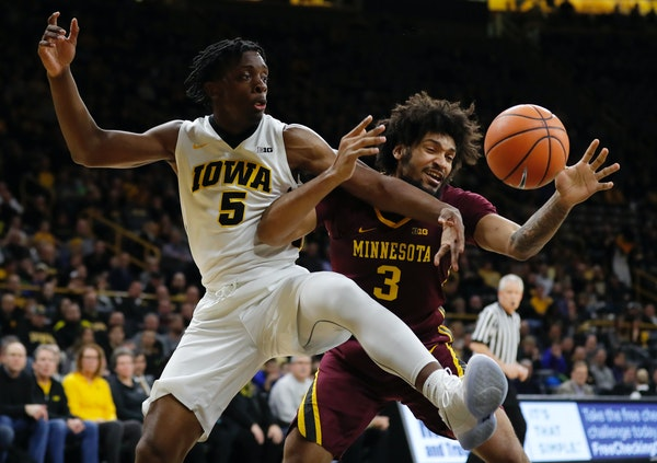 Iowa forward Tyler Cook, left, fights for a rebound with Minnesota forward Jordan Murphy (3) during the first half of an NCAA college basketball game,