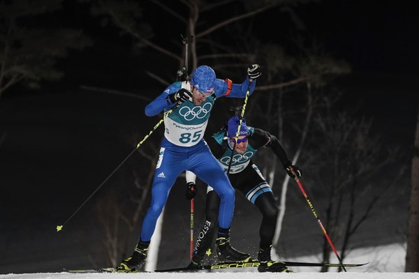 Leif Nordgren, of the United States, climbs ahead Kauri Koiv, of Estonia, during the men's 10-kilometer biathlon sprint at the 2018 Winter Olympics in