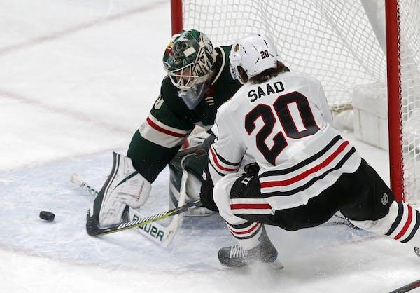Minnesota Wild goalie Devan Dubnyk stops a shot by Chicago Blackhawks' Brandon Saad, right, in the first period.