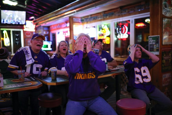 Richard Holmes, foreground left, and Gavin Smith, right, reacted to a Eagles interception and run back of a Vikings pass for a first quarter touchdown