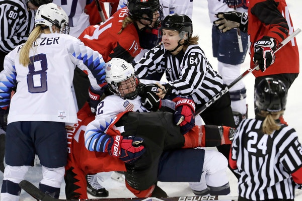 Official Jenni Heikkinen (64), of Finland, tries to separate Kelly Pannek (12), of the United States, and Laura Stacey (7), of Canada, as they scuffle