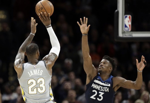 Cleveland Cavaliers' LeBron James, left, shoots over Minnesota Timberwolves' Jimmy Butler for the game-winning basket in overtime of an NBA basketball