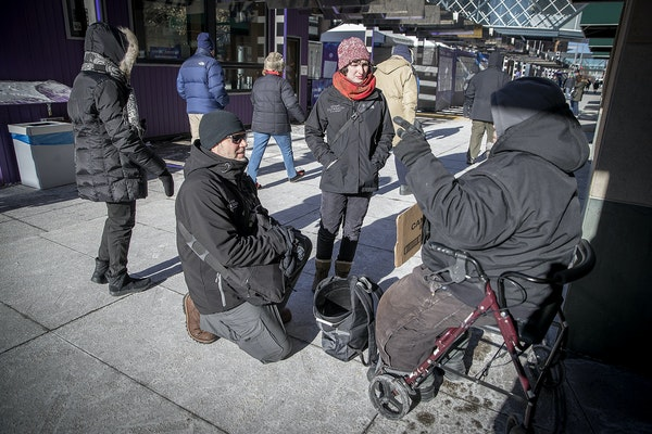 John Tribbett, left, and Ilana Budenosky, cq, with the St. Stephen's Street Outreach met with a man who was panhandling along Nicollet Mall, Thursday,
