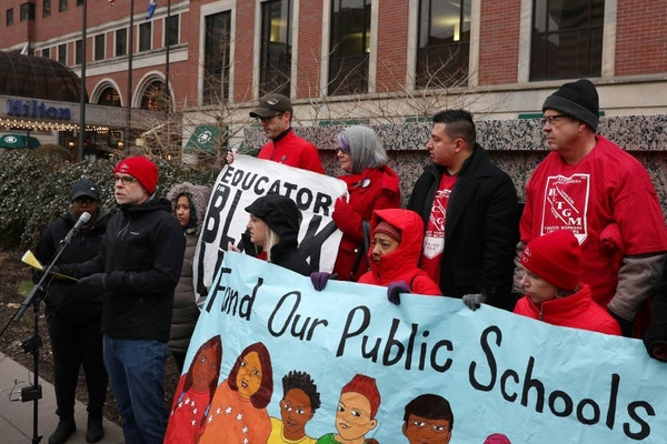 Nick Faber, president of the St. Paul Federation of Teachers, spoke as others held signs while they protested at a CEO luncheon outside the Hilton hot