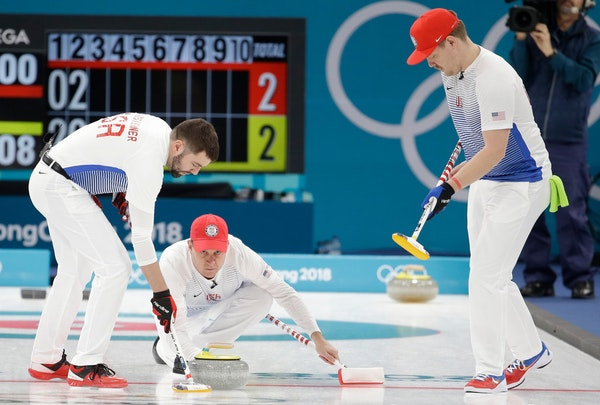 United States's skip John Shuster, center, throws a stone as teammates John Landsteiner, left, and Matt Hamilton prepare to sweep the ice during a men