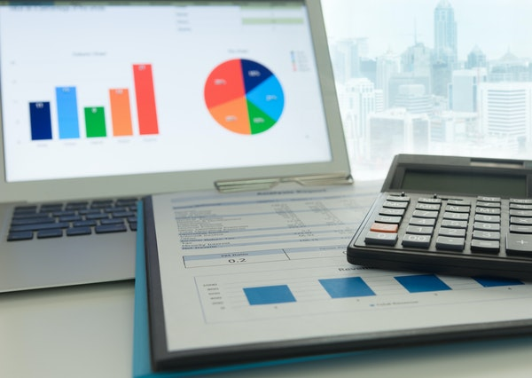 Financial planning accounting concept. Calculator on business and financial report on desk of entrepreneur. istock