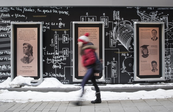 A student walks past a plaque with musician Dessa Wander's picture and story (left) on Scholars Walk at the University of Minnesota campus on Monday,