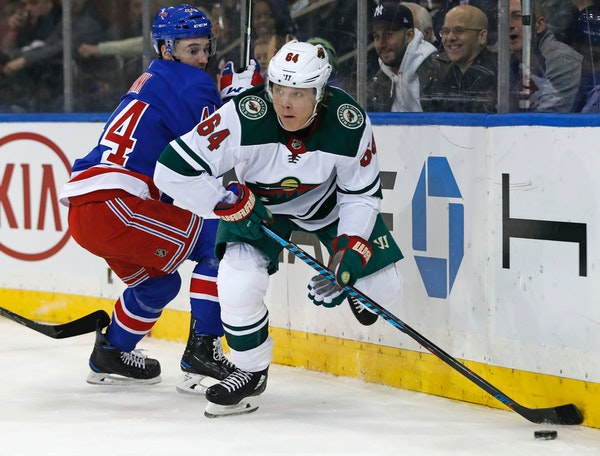 With New York Rangers defenseman Neal Pionk (44) looking on, Minnesota Wild right wing Mikael Granlund (64) looks to pass during the first period of a