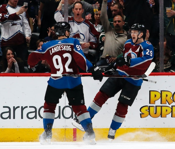 Colorado Avalanche left wing Gabriel Landeskog, left, celebrates with center Nathan MacKinnon after his goal against the Minnesota Wild in the second