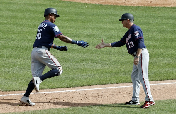 Minnesota Twins' Ehire Adrianza (16) is congratulated by third base coach Gene Glynn (13) after hitting a two-run home run during the fifth inning o