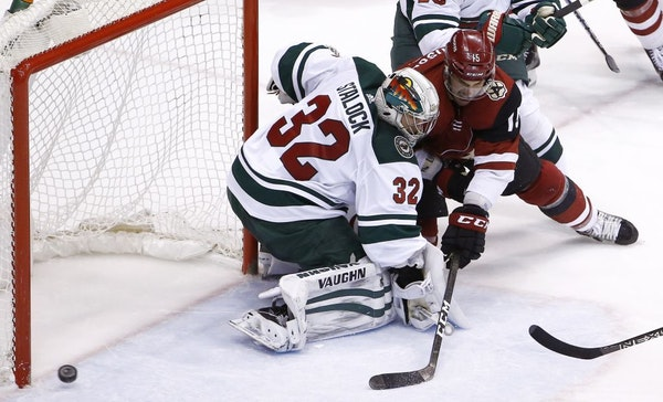 Arizona Coyotes center Brad Richardson, right, sends the puck just wide of Minnesota Wild goaltender Alex Stalock (32) during the second period of an