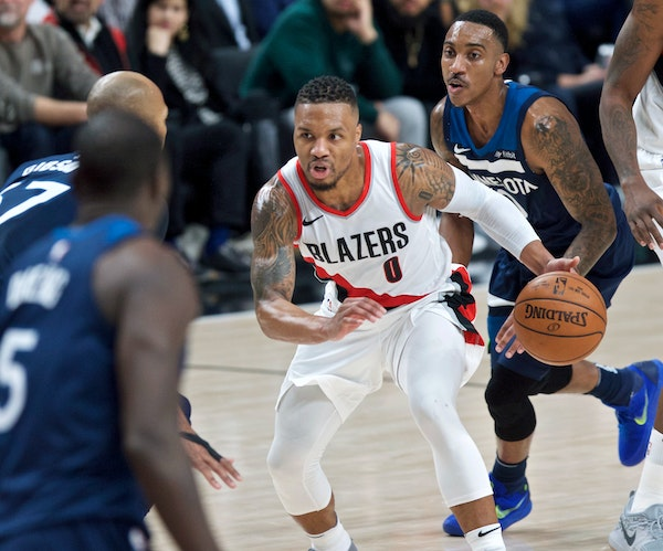 Portland Trail Blazers guard Damian Lillard dribbles as the Minnesota Timberwolves including guard Jeff Teague, right, watch during the second half of