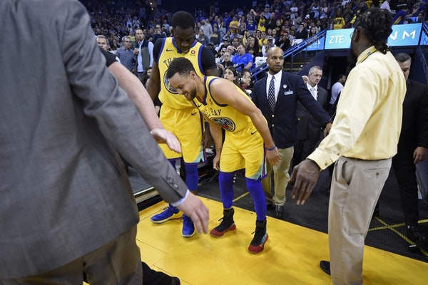 Golden State Warriors' Stephen Curry (30) limps back to the court after injuring his right ankle as teammate Draymond Green (23) checks on his conditi