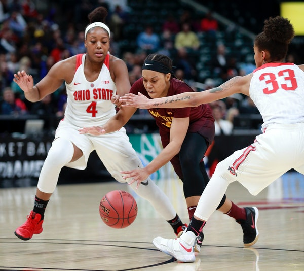 Minnesota guard Gadiva Hubbard dribbles between Ohio State guards Jensen Caretti (33) and Sierra Calhoun during the first half of an NCAA college bask