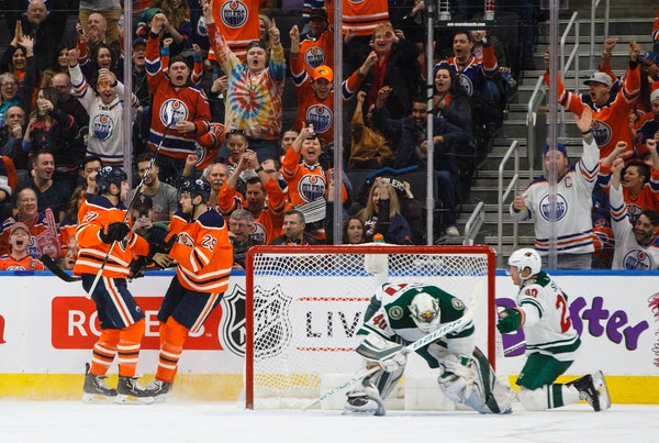 Minnesota Wild goaltender Devan Dubnyk (40) and defenseman Ryan Suter (20) react as Edmonton Oilers left wing Milan Lucic (27) and center Leon Draisai