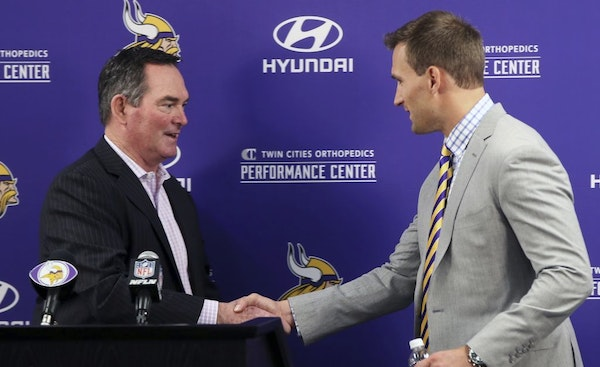 Minnesota Vikings new quarterback Kirk Cousins, right, is welcomed to the podium by head coach Mike Zimmer before addressing the media at a news confe