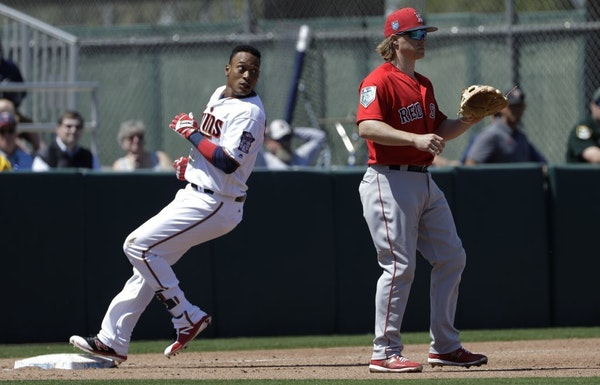 Minnesota Twins' Jorge Polanco, left, goes into third base ahead of the throw to Boston Red Sox's Brock Holt after hitting a triple off Red Sox pitche