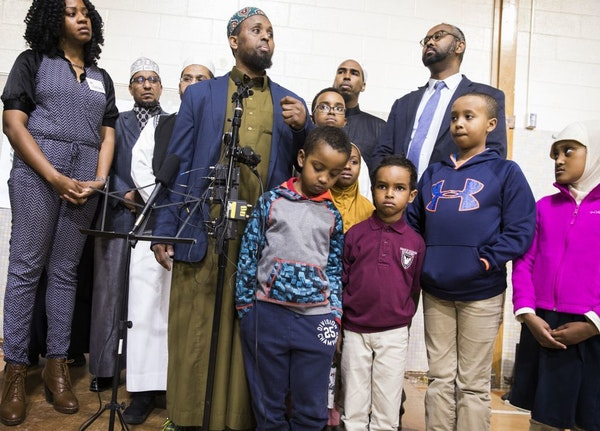 Dar Al Farooq Islamic Center Executive Director Mohamed Omar, center, spoke about the charges filed against three people in the bombing of the mosque