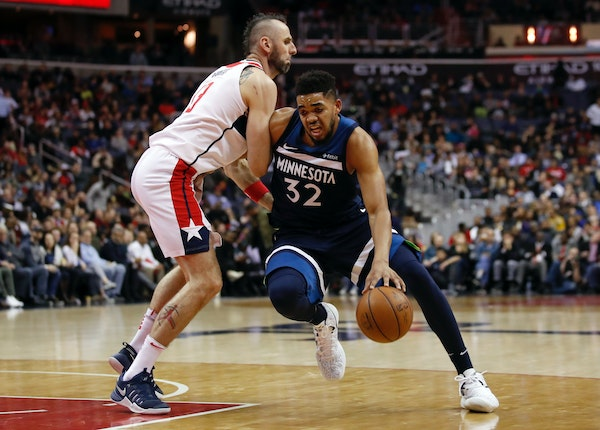 Timberwolves center Karl-Anthony Towns (32) drives against Wizards center Marcin Gortat during the first half of Tuesday's game.