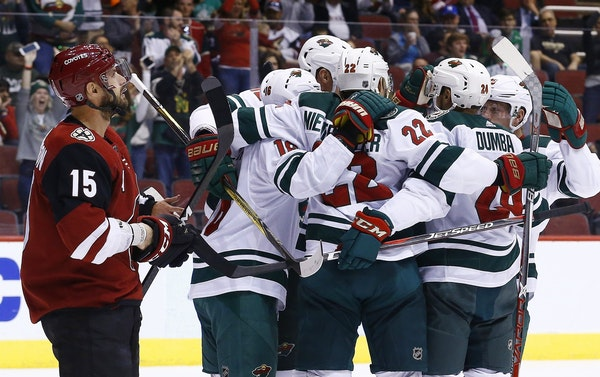 Wild players surrounded Nino Niederreiter (22) after he scored the first goal of Saturday night's game at Arizona.