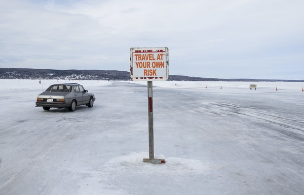 Cars traveled Monday on the ice road from Madeline Island to Bayfield, seen in the distance.