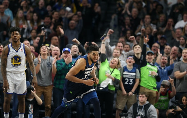 Timberwolves center Karl-Anthony Towns celebrated as Warriors guard Nick Young (6) looked on late in the fourth period of Minnesota's 109-103 victory