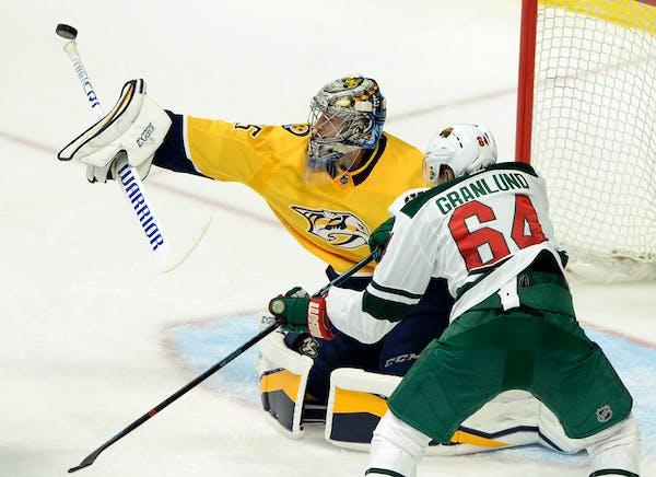 Nashville Predators goaltender Pekka Rinne (35), of Finland, blocks a shot with his stick as Minnesota Wild right wing Mikael Granlund (64), of Finlan