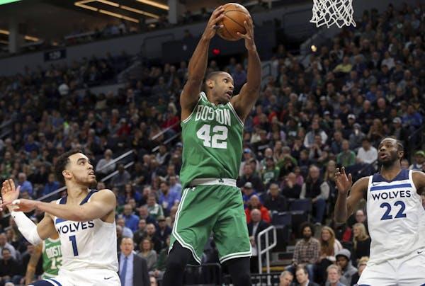 Boston Celtics's Al Horford, center, of Dominican Republic, pulls in a rebound as Minnesota Timberwolves' Tyus Jones, left, and Andrew Wiggins, ri