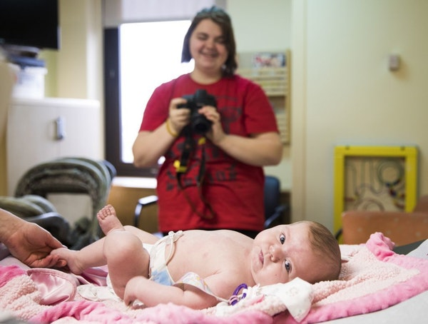 Chelsea Ohlquist takes photos of her infant daughter Corah after an electrocardiogram.