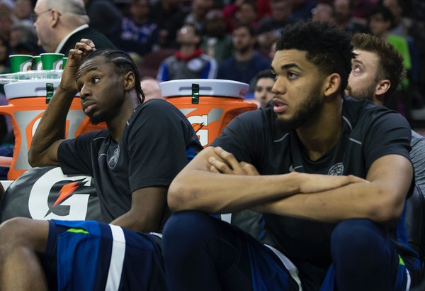 Minnesota Timberwolves' Andrew Wiggins, left, and Karl-Anthony Towns, right, sit on the bench during the second half of the team's NBA basketball game
