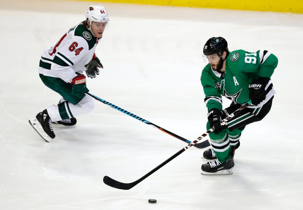 Minnesota Wild's Mikael Granlund (64) defends as Dallas Stars center Tyler Seguin (91) handles the puck in the third period of an NHL hockey game in D
