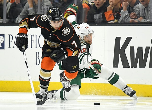Anaheim Ducks left wing Andrew Cogliano, left, takes the puck next to Minnesota Wild left wing Jason Zucker during the second period of an NHL hockey