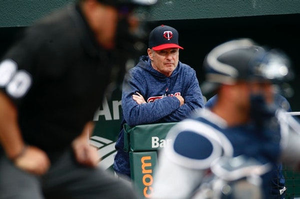 Minnesota Twins manager Paul Molitor is seen past home plate umpire Marty Foster, front left, and Twins catcher Mitch Garver as he watches the seventh