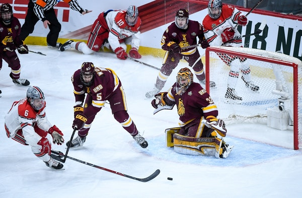 Minnesota Duluth goaltender Hunter Shepard eyed the puck as defenseman Nick Wolff and Ohio State defenseman Tommy Parran (6) battled in front of the n