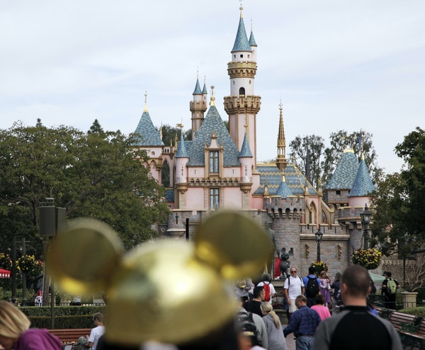 In this 2015 file photo, visitors walk toward the Sleeping Beauty's Castle in the background at Disneyland Resprt in Anaheim, Calif. Visiting Mickey a